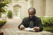 Man reading BIble outdoors
