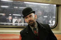 a man on a train with a top hat and mustache