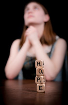 Bokeh view of a woman praying behind stacked block letters spelling hope.