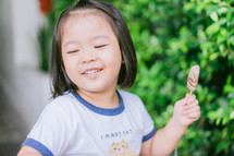 a toddler girl eating chocolate ice cream on a stick