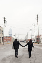 man and woman holding hands walking down an urban street