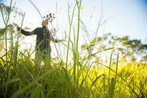man with outstretched arms standing in tall grass