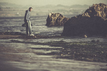 A man walking along a rocky shore.