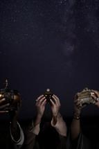 wisemen holding up gold, frankincense, and myrrh