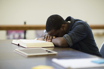 an exhausted man with his head on a book in a library