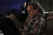 man with dreads sitting on a couch reading a Book