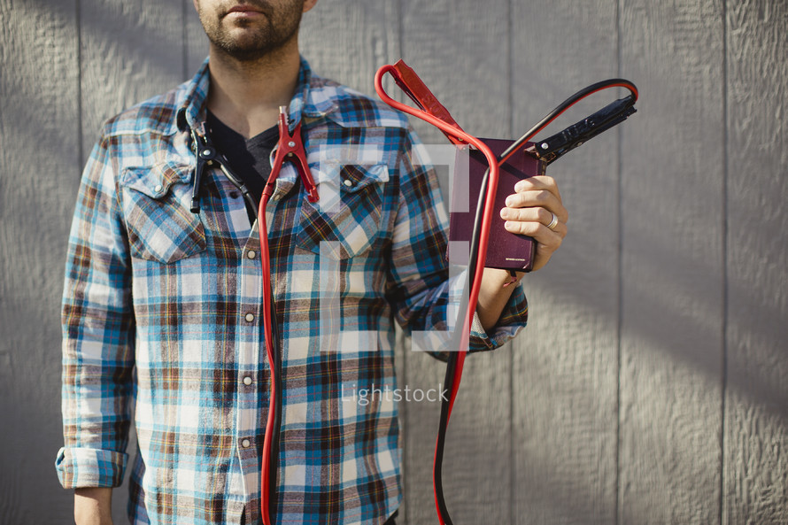 Man holding Bible with jumper cables attached from corners of Bible to his shirt collar.