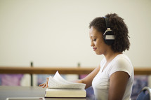 a woman reading and listening to headphones