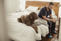 Man sitting on side of bed with dog with head bowed praying.