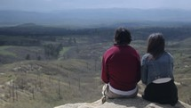 couple sitting on the edge of a mountain looking out and enjoying the view
