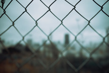 Chain linked fence in a city | Bokeh | Cinematic | World | Day | Cloudy | Sky | Town | Restricted | Youth