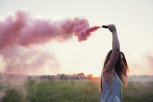 a young woman holding a pink smoke flare.