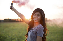 young woman holding a smoke flare at sunset