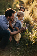 a mother and father exploring the outdoors with their toddler son
