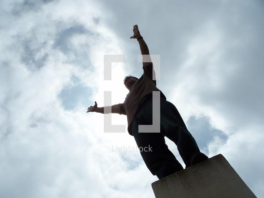 man standing with arms raised in worship to God