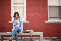 a woman sitting on a stone bench looking at her cellphone