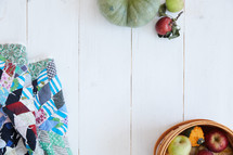quilt, basket of apples, and pumpkins on a white wood boards