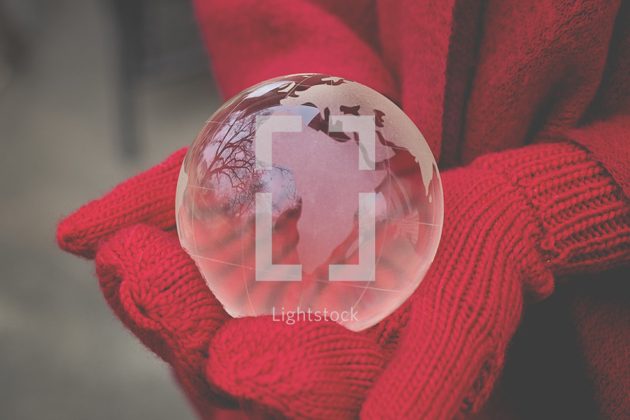 gloved hands holding a glass globe