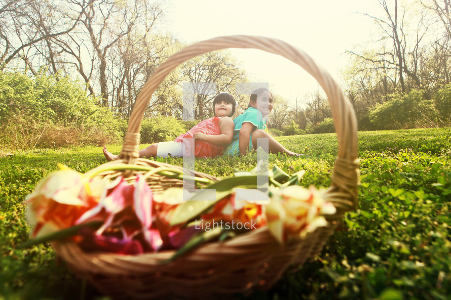 Girls sitting in a field with a flower basket