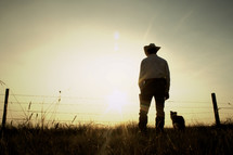 A rancher and his dog in a field at sunset