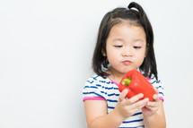 a little girl holding a pepper