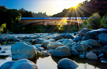 Sunrise over bridge and rocks in creek.