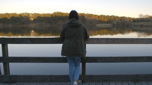a woman looking over a railing on a dock
