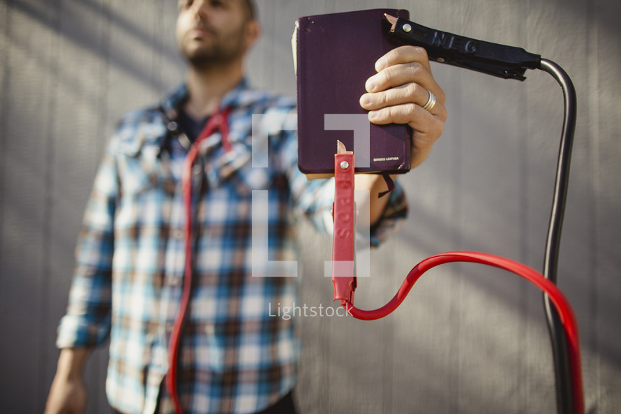 Man holding Bible with jumper cables attached.