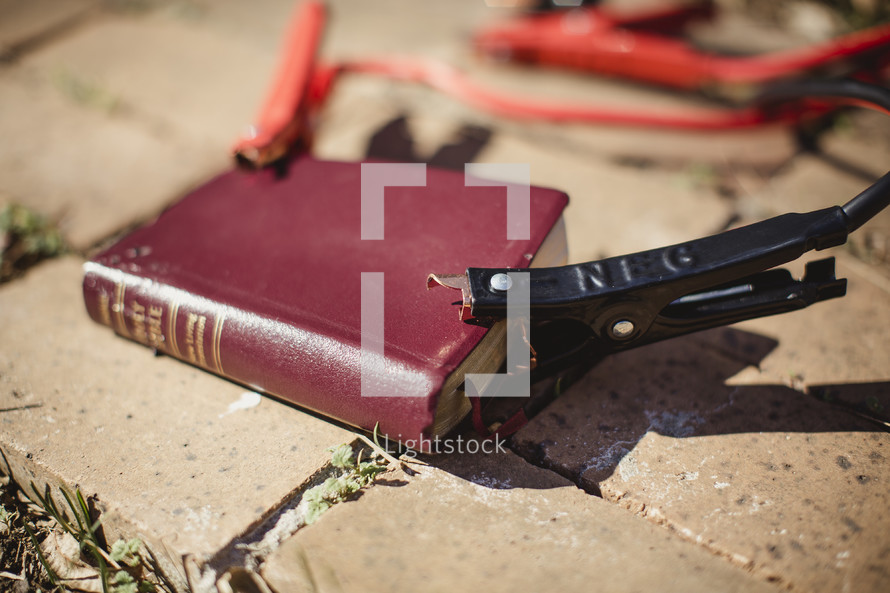 Red Bible laying on brick sidewalk with jumper cables attached.