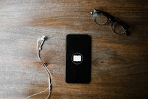 earbuds, cellphone, Bible app, and reading glasses on a wood table