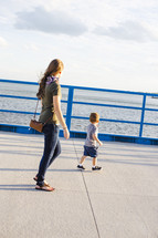 a mother and son walking on a harbor sidewalk