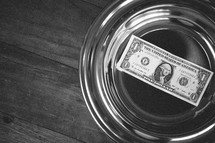 single dollar in an offering plate
