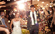 Bride and groom leaving wedding ceremony running in confetti