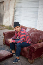 Young man in jeans with hat sitting on old sofa in alley outside garage door.
