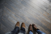 feet of a couple on floor boards