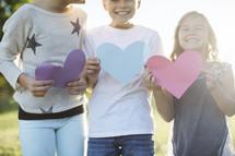 children holing paper heart shapes