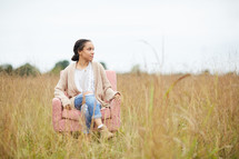 a woman sitting in a chair in a field