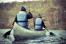 men paddling a canoe in fall