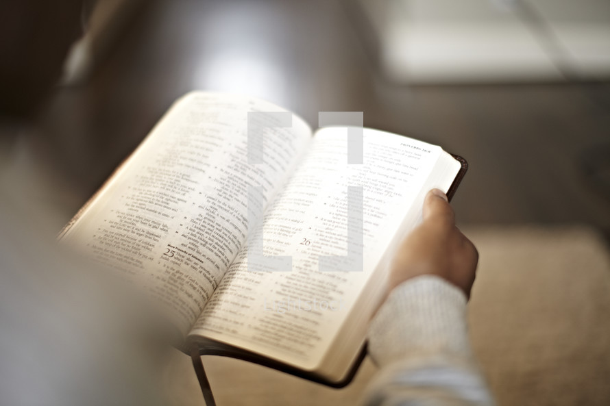 An over-the-shoulder view of a man reading a bible