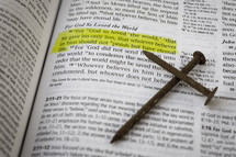 John 3:16 and a cross of nails on the pages of a Bible