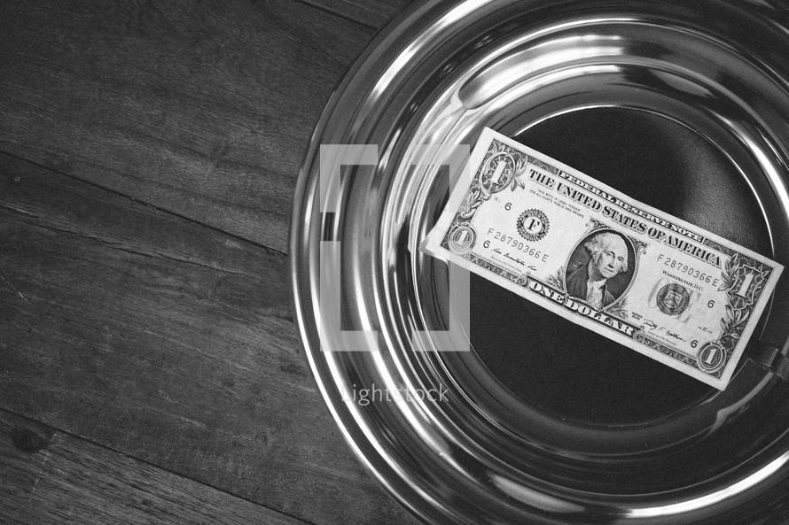 single dollar in an offering plate