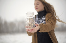 a woman holding a mason jar full of fairy lights outdoors in the snow