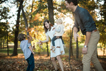 a young family playing in fall leaves