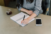 a businesswoman sitting at a desk writing notes in a planner