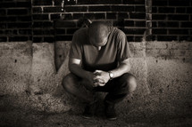 A young man kneeling in prayer