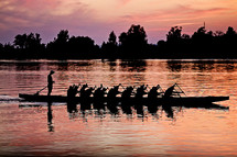silhouette of rowers paddling a boat at sunset