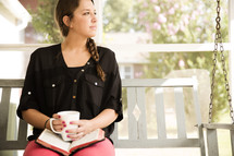 woman on a porch swing with a Bible and coffee