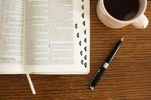 pen, Bible, and coffee mug on a table