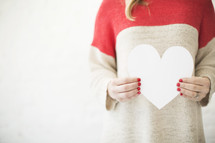 Woman in a red and white sweater holds a white paper heart.