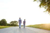 a father and son walking and talking down a rural road